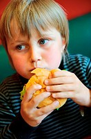 Stock photo of an 11 year old boy eating a burger
