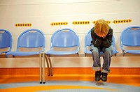 Stock photo of an 11 year old boy holding his head in his hands sitting on a waiting room chair