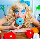 Blonde funny girl on kitchen eating blue donut with fashion makeup