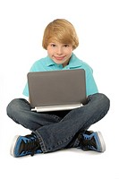Eleven year old boy sitting and using laptop computer