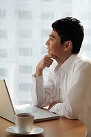 Young man sitting with laptop looking out window