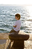 Boy contemplating sea on harbur at sunset