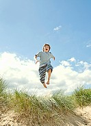Boy leaping over grass on beach