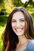 Smiling woman with flower in park