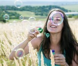 Woman blowing bubbles in wheatfield