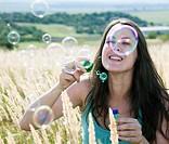 Woman blowing bubbles in wheatfield