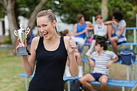 Woman holding trophy in park
