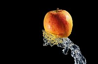 Splashing water on red apple