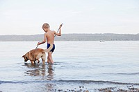 Boy wading with dog on beach