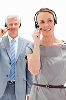 Close_up of a woman wearing a headset with a white hair businessman in the background
