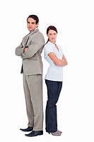 Serious salesteam with arms folded standing back to back against a white background