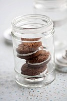 Three chocolate whoopie pies stacked in a glass jar