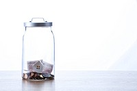 European union currency and model house inside of glass jar