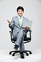 Asian Businessman Sitting On Chair With Leg Crossed Holding Laptop In Hand