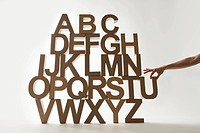 Hand reaching for letter in stacked alphabet