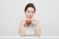 Asian Businesswoman Sitting In Front Of Desk With Head On Hand