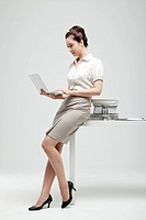 Asian Businesswoman Sitting On Desk With Books And Hour Glass Working On Laptop