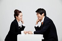 Asian Businessman And Businesswoman At Desk Facing Each Other With Hand On Chin