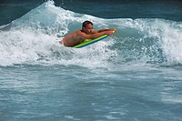 Teenager surfing the beach with a Boogie_Board.
