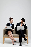 Asian Businesswoman And Businessman Sitting On Sofa Using Laptop
