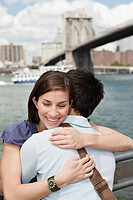 Couple hugging in front of Brooklyn Bridge, New York City, USA