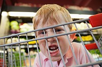 Close up of boy 5-6 making faces behind shopping cart (thumbnail)