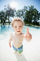 Portrait of smiling boy 3_4 wading in water and pointing with finger