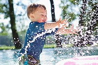Boy 3_4 splashing water in pool