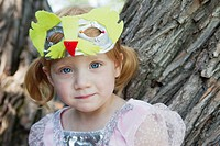Portrait of girl 3-4 with face mask sitting on tree (thumbnail)