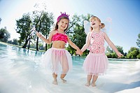 Two girls 3-4 in costumes playing at pool (thumbnail)