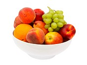 White china bowl filled with fresh fruit, grapes, oranges, peaches, pears, apples and nectarines, on a white background.