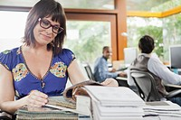 Woman arranging notebooks in office