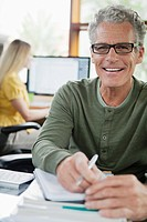 Portrait of smiling man working at desk in office