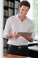 Portrait of mid adult man holding tablet pc (thumbnail)