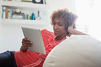 Portrait of smiling woman using digital tablet on sofa