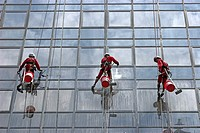 High rise window cleaners work suspended on ropes Orchard Road Singapore