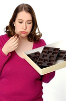 Humorous photo of a woman who has eaten a large box of chocolates and is feeling sick and bloated