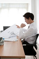 Businessman looking at blueprint at desk