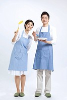 Young couple in apron holding kitchen utensil