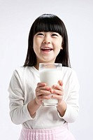 Little girl holding a glass of milk