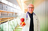 A middle aged doctor holding some fruit and vegetables inside a hospital.