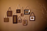Interior wall with different size and shaped frames hanging from ribbons.