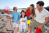 Happy family with fishing net and pails on sunny beach