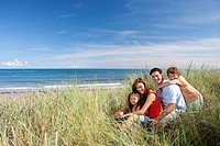 Portrait of smiling family sitting in grass on beach