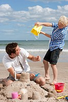 Father and son making sandcastle on sunny beach