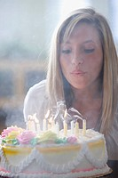 Caucasian teenage girl blowing out birthday candles