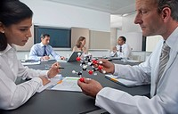 Scientist and businesswoman examining molecular model in conference room