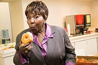 Black businesswoman eating donuts in office
