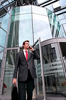 young caucasian businessman at office exterior talking on cellph