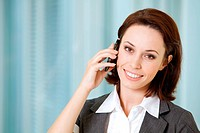 Portrait of young caucasian businesswoman talking on cellphone in offucw